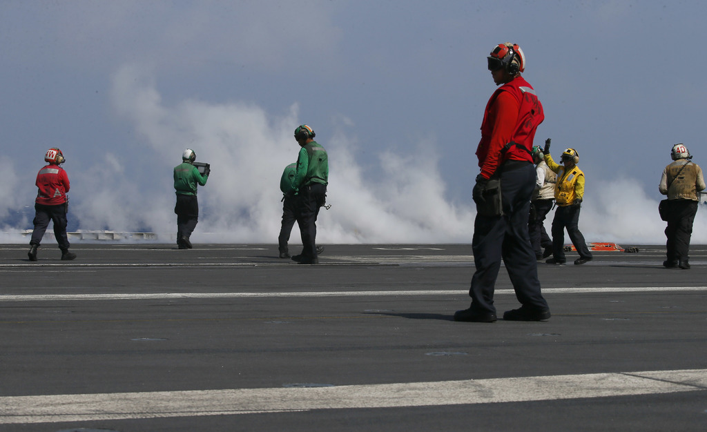 With smoke created by a F18 fighter jet taking off crewmen prepare the next one aboard the U.S. Navy aircraft carrier USS Carl Vinson (...