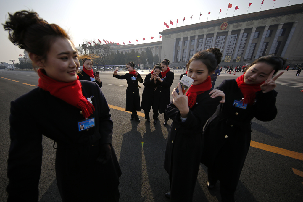 In this Friday, March 3, 2017, photo, bus ushers take selfies on an empty street adjacent to the Great Hall of the People during the Ch...