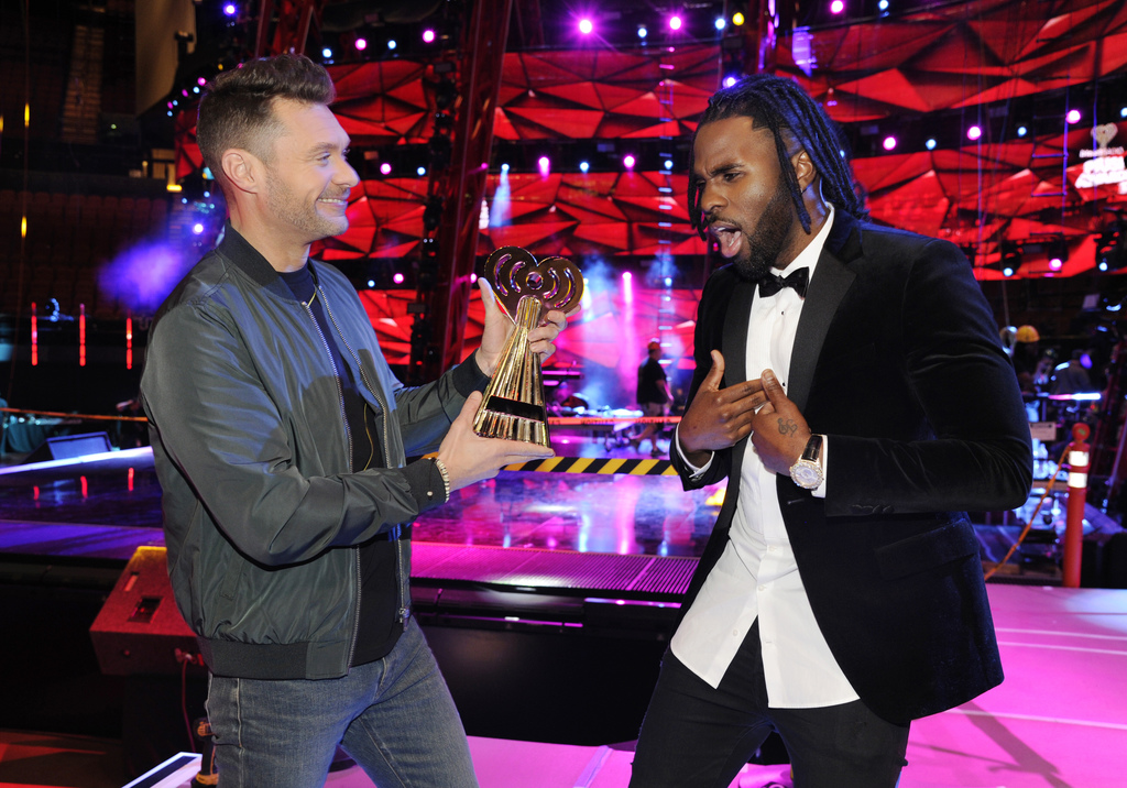 Host Ryan Seacrest, left, pretends to hand an award to singer Jason Derulo at the press preview day for the 2017 iHeartRadio Music Awar...
