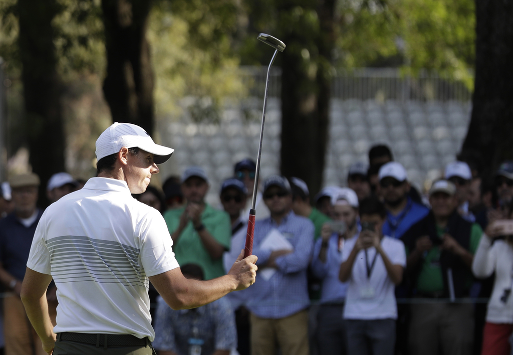 Rory McIlroy of Northern Ireland gestures to fans with his club as he leaves the 9th hole after finishing round one of the Mexico Champ...