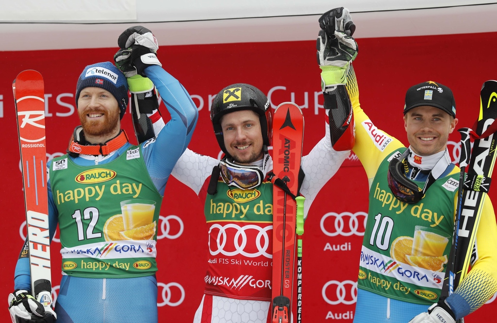 Austria's Marcel Hirscher, center, winner of an alpine ski, men's World Cup giant slalom, celebrates on the podium with second-placed N...