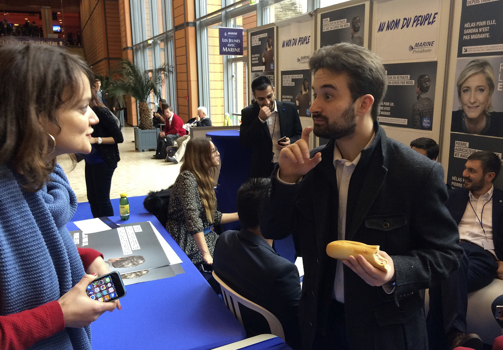 In this Feb. 5, 2017 photo, Davy Rodriguez, a former hard-left activist, talks on the National Front for Youth stand in Lyon. Ex-commun...