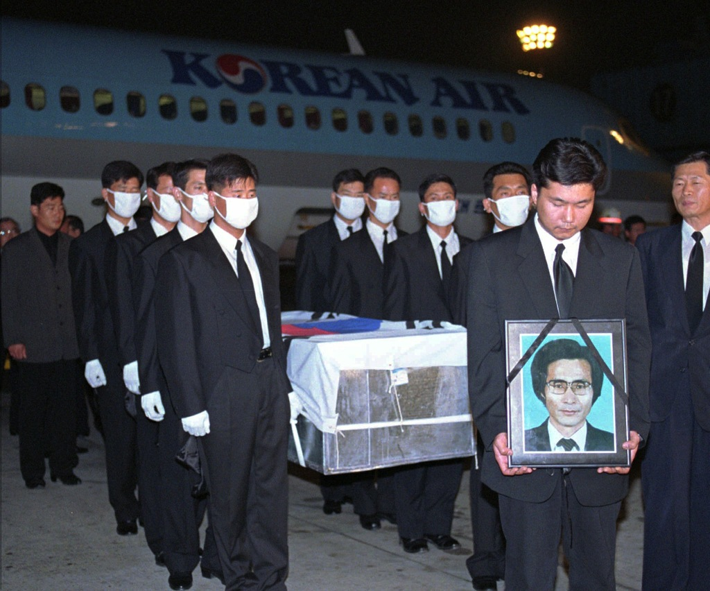 FILE - In this Oct. 5,1996 file photo, government officers carry a portrait and a coffin containing South Korean Choi Duk-kun, a South ...