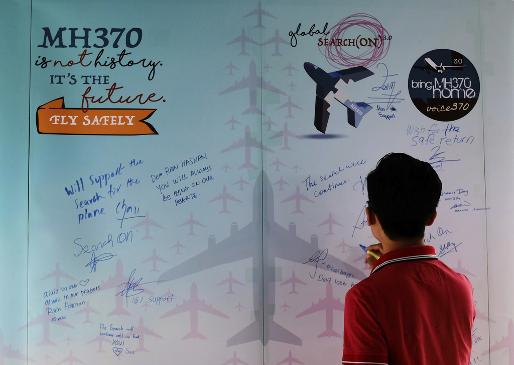A man writes a condolence message during the Day of Remembrance for MH370 event in Kuala Lumpur, Malaysia on Saturday, March 4, 2017. A...
