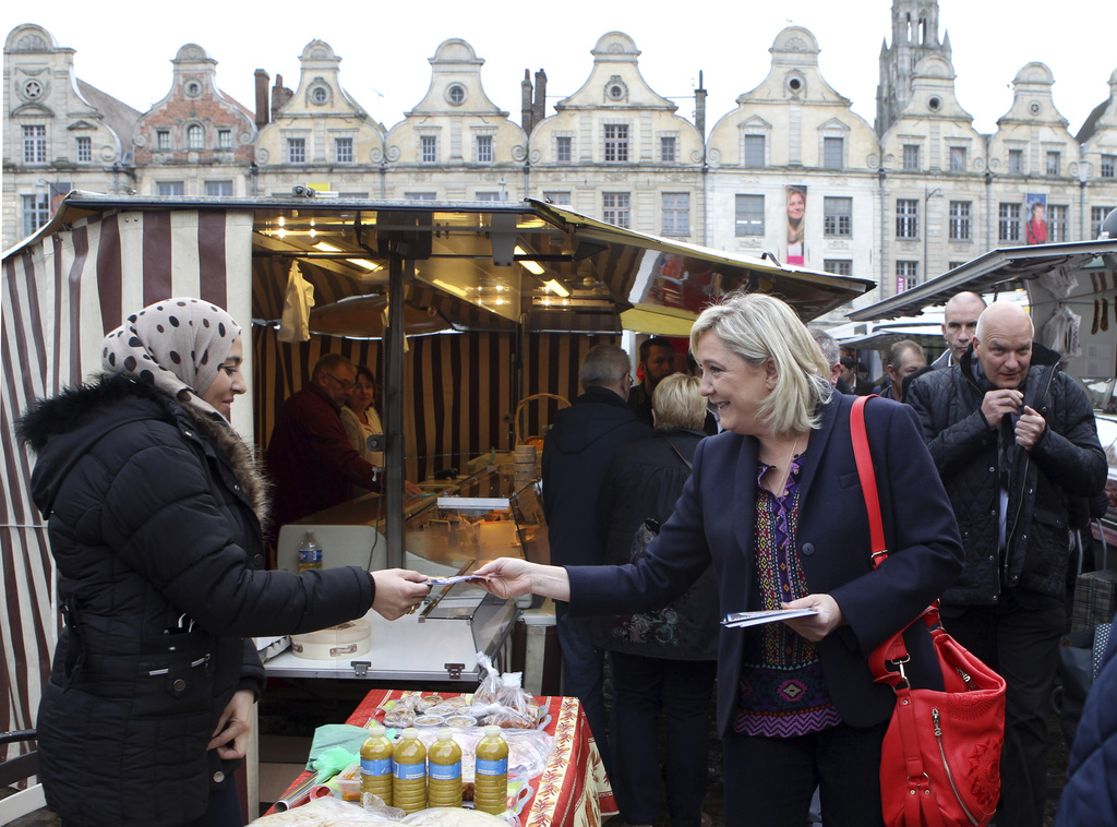 FILE - In this Nov. 7, 2015 file photo, French far-right leader Marine Le Pen hands out leaflets in a marketplace, in Arras northern Fr...