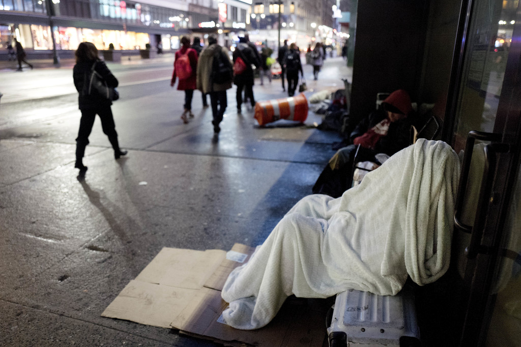 FILE - In this Jan. 11, 2017 file photo, a homeless person sleeps under a blanket on a New York sidewalk. Mayor Bill de Blasio plans to...