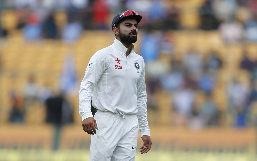 India's captain Virat Kohli reacts after a catch drop by teammate Ajinkya Rahane during the first day of their second test cricket matc...