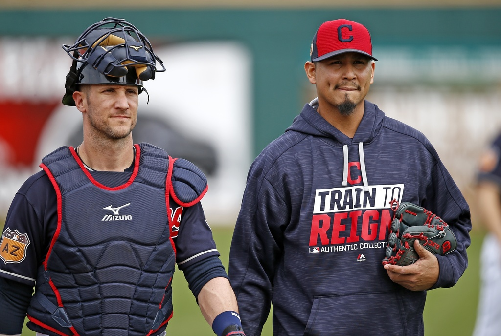 Cleveland Indians starting pitcher Carlos Carrasco, right, walks in from the bullpen with catcher Yan Gomes, left, after warming up for...