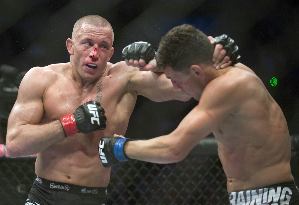 FILE - In this March 16, 2013, file photo, Georges St. Pierre, left, lands a blow to Nick Diaz, from the United States, during their UF...