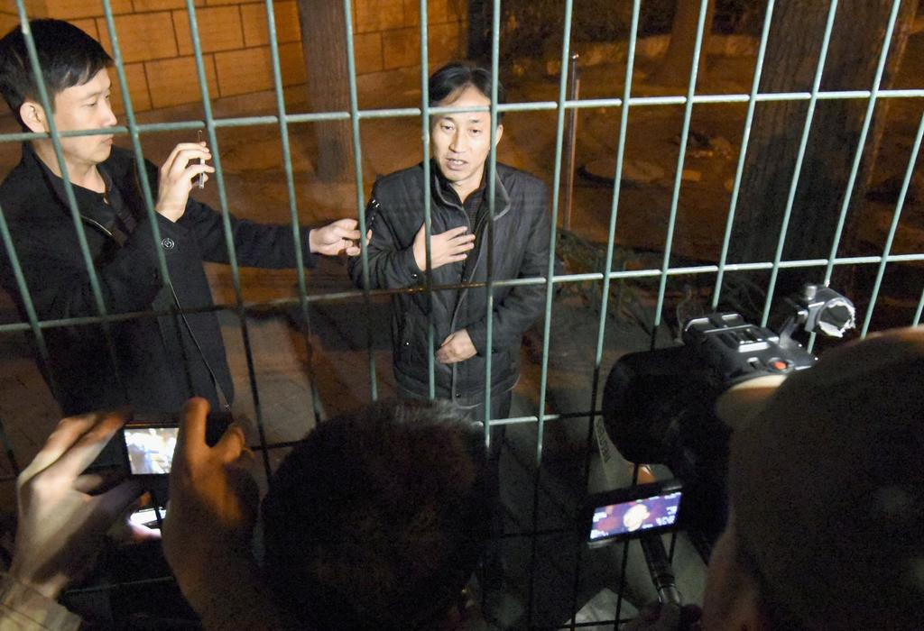 North Korean Ri Jong Chol, right, speaks to reporters from behind a fence at the North Korean Embassy in Beijing early Saturday, March ...