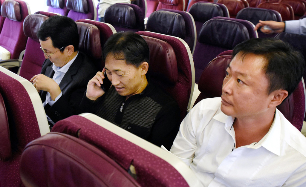 In this Friday, March 3, 2017 photo, North Korean Ri Jong Chol, center, waits for the departure inside a plane bound for Beijing, China...