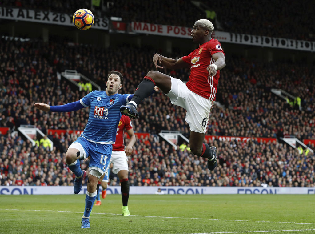 AFC Bournemouth's Adam Smith, left, and Manchester United's Paul Pogba battle for the ball during their English Premier League soccer m...