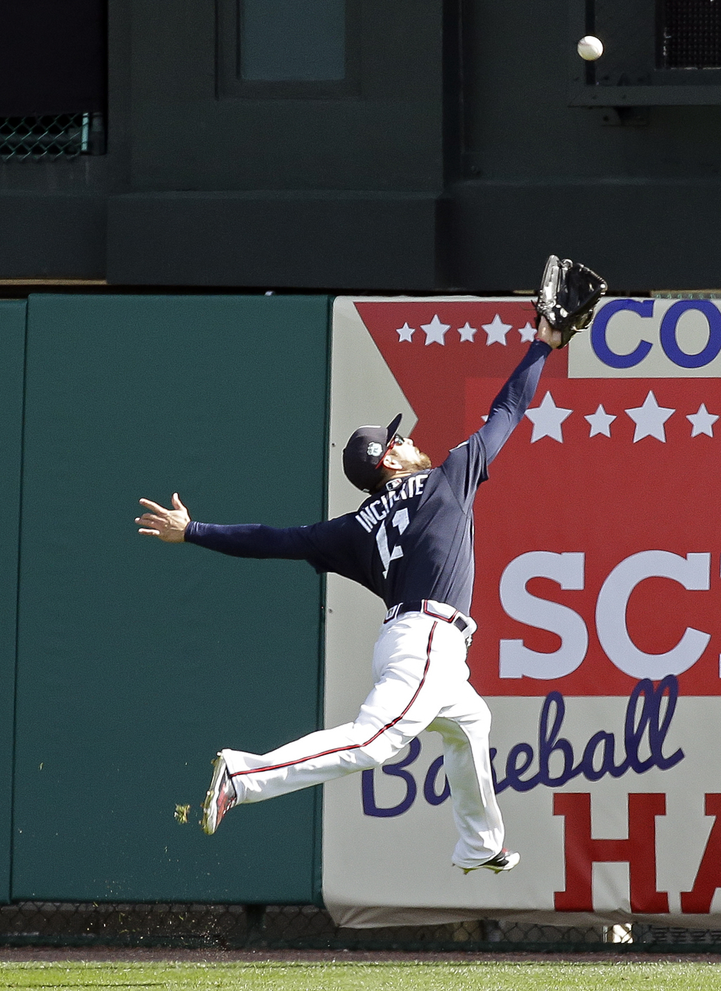 ADDS INNING - Atlanta Braves center fielder Ender Inciarte (11) leaps but can't make the catch on a fly ball over his head during the f...