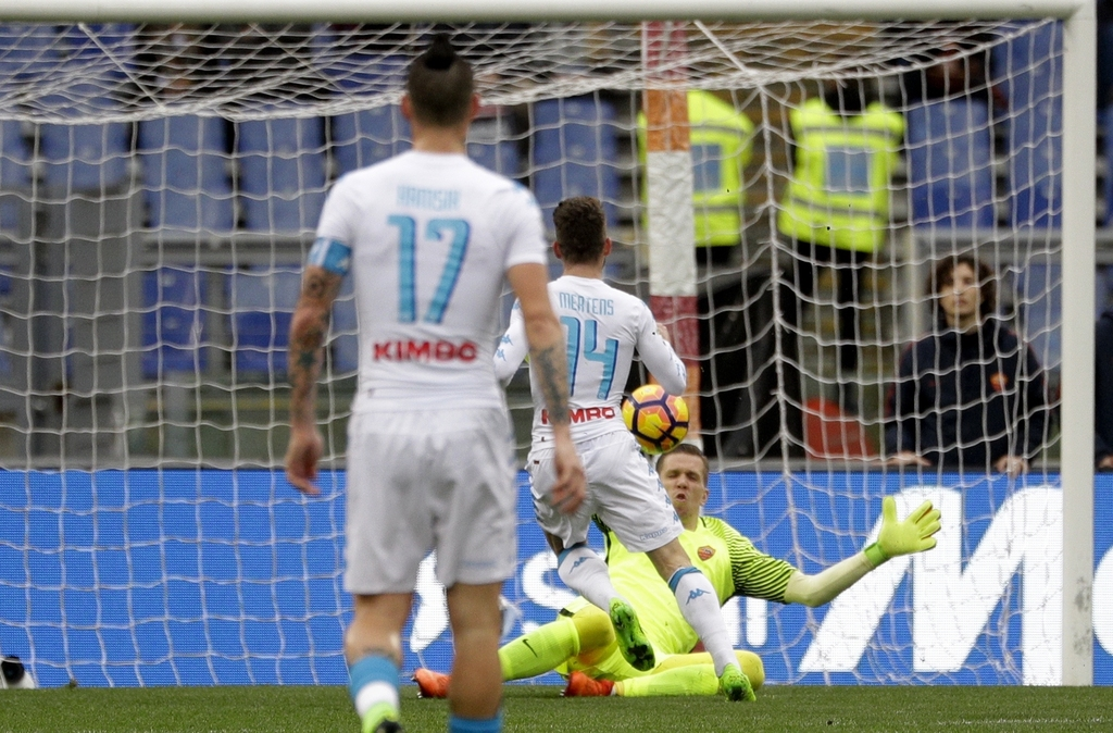 Napoli's Dries Mertens scores past Roma goalkeeper Wojciech Szczesny during a Serie A soccer match, at the Rome Olympic stadium, Saturd...