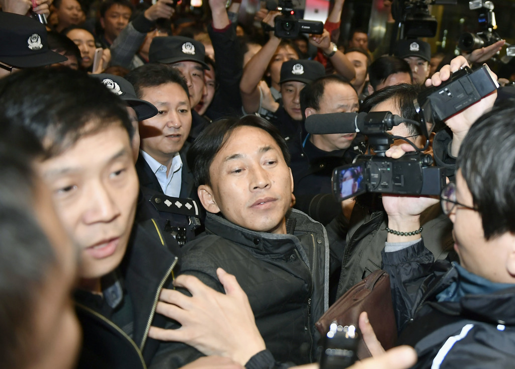 North Korean Ri Jong Chol, front center, detained in the killing of the half brother of North Korea's leader, arrives at Beijing Capita...