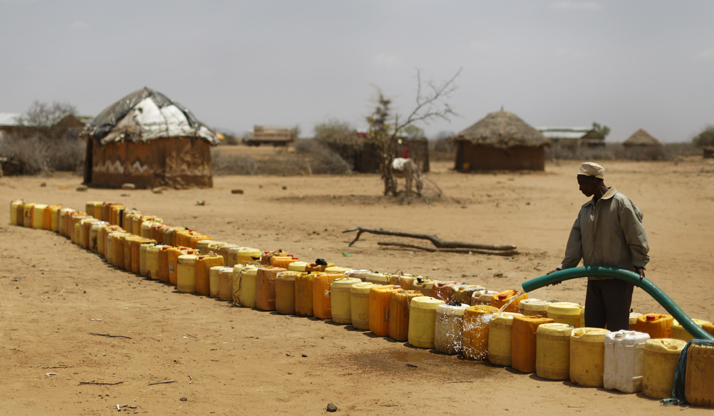 A man fills a long line of plastic water containers from a tanker, in the drought-affected village of Bandarero, near Moyale town on th...