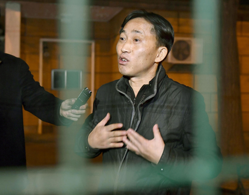 North Korean Ri Jong Chol speaks to reporters from behind a fence at the North Korean Embassy in Beijing early Saturday, March 4, 2017....