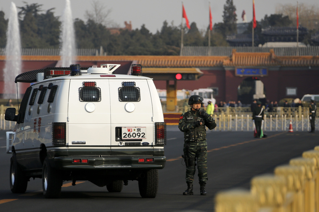 A Chinese paramilitary policeman stands watch near the Great Hall of the People as delegates from China's People's Liberation Army (PLA...