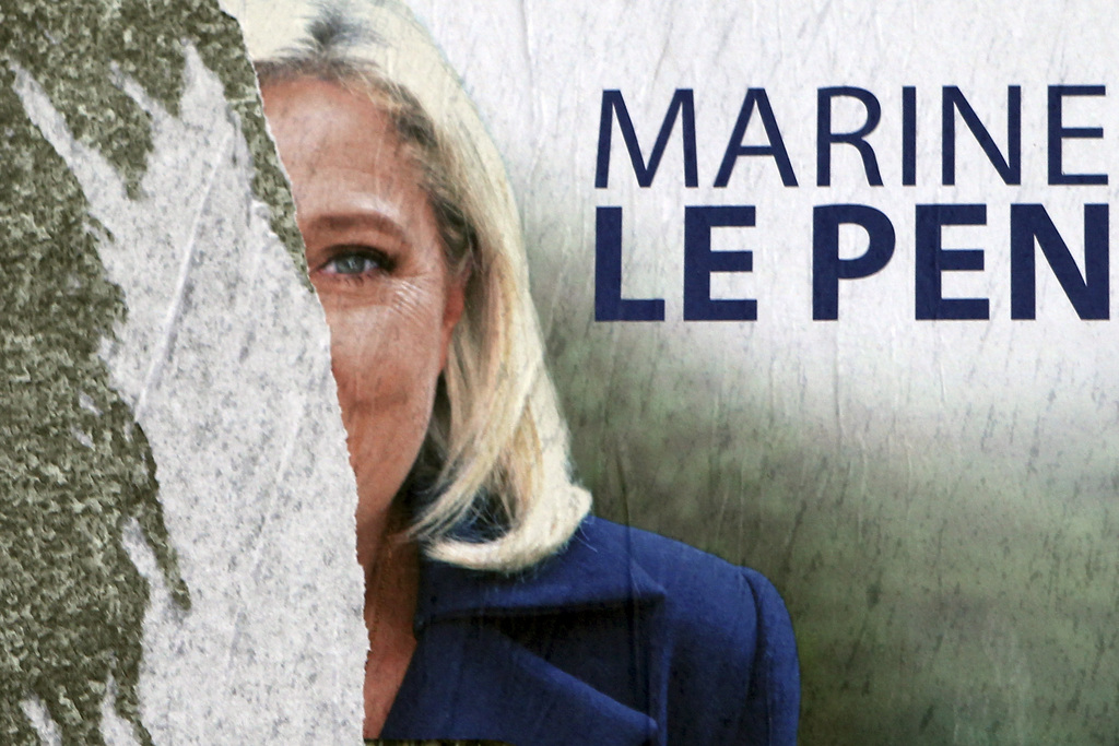 FILE - In this Dec. 11, 2015 file photo, a defaced poster of French far-right party leader Marine Le Pen is seen in Henin-Beaumont, nor...