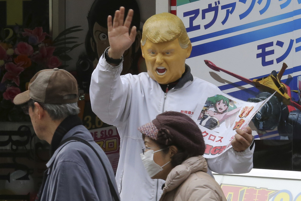 Saturday, March 4, 2017, photo, an employee advertising for a pachinko gaming parlor wears a President Donald Trump mask to attract cus...