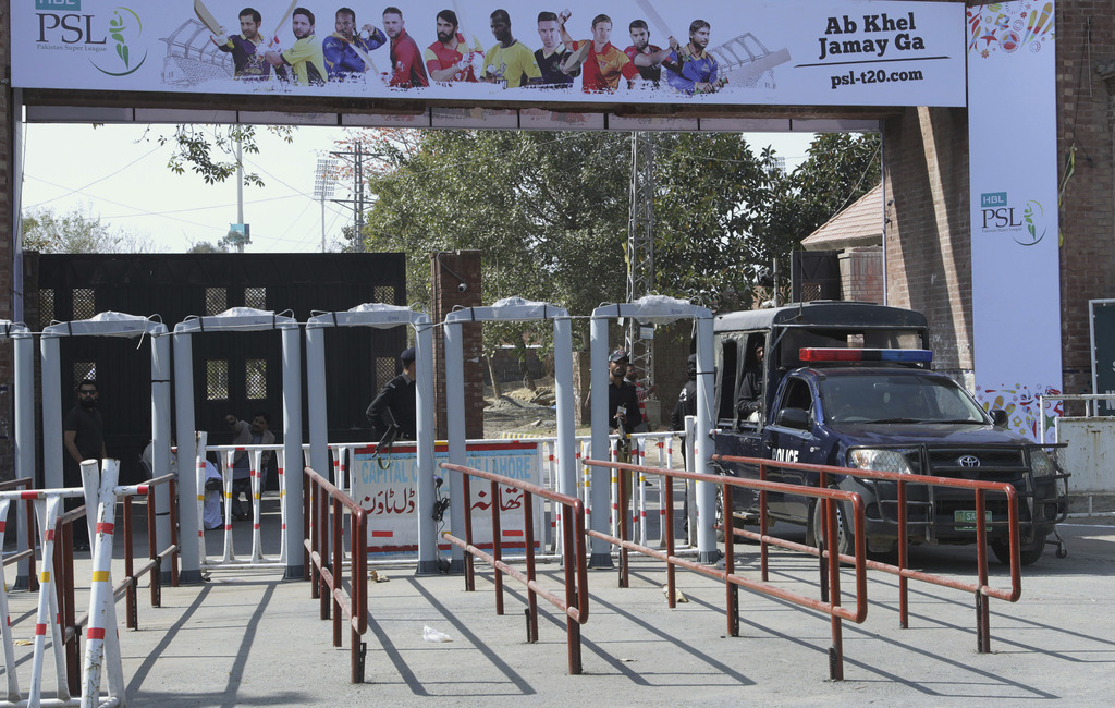 Pakistani police officers stand guard beside walk through metal detector specially installed at an entry gate of Gaddafi stadium for th...