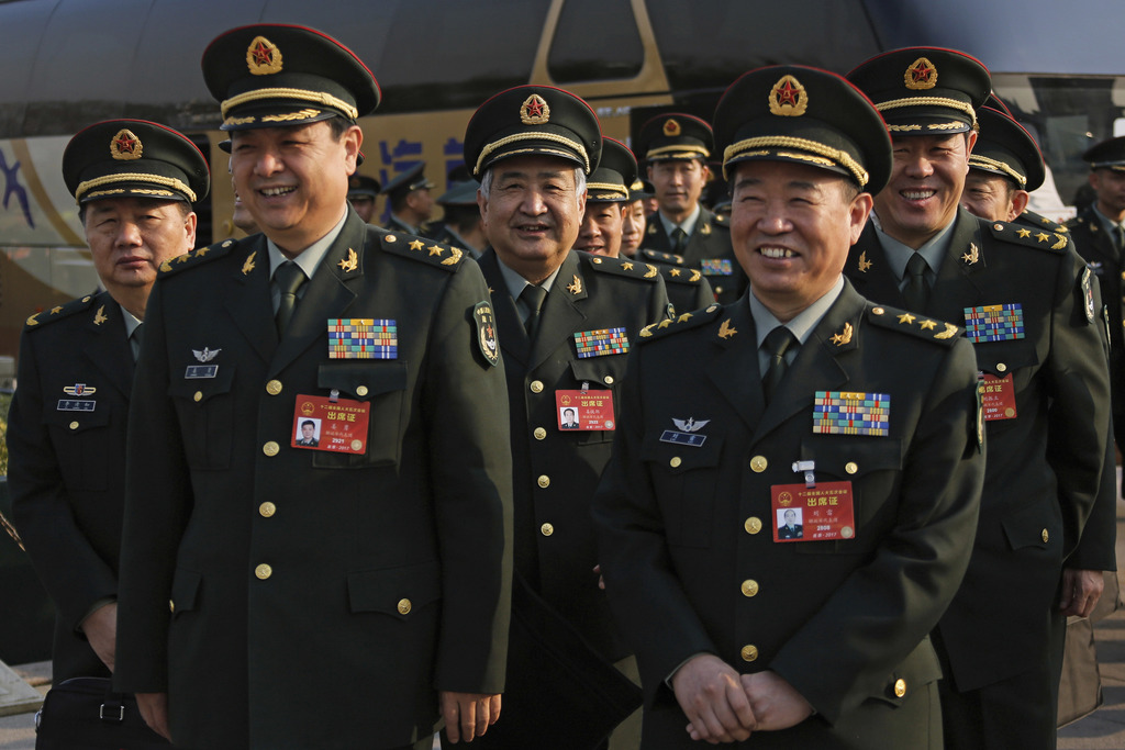 Delegates from China's People's Liberation Army (PLA) share a light moment as they arrive to attend a plenary session of the National P...