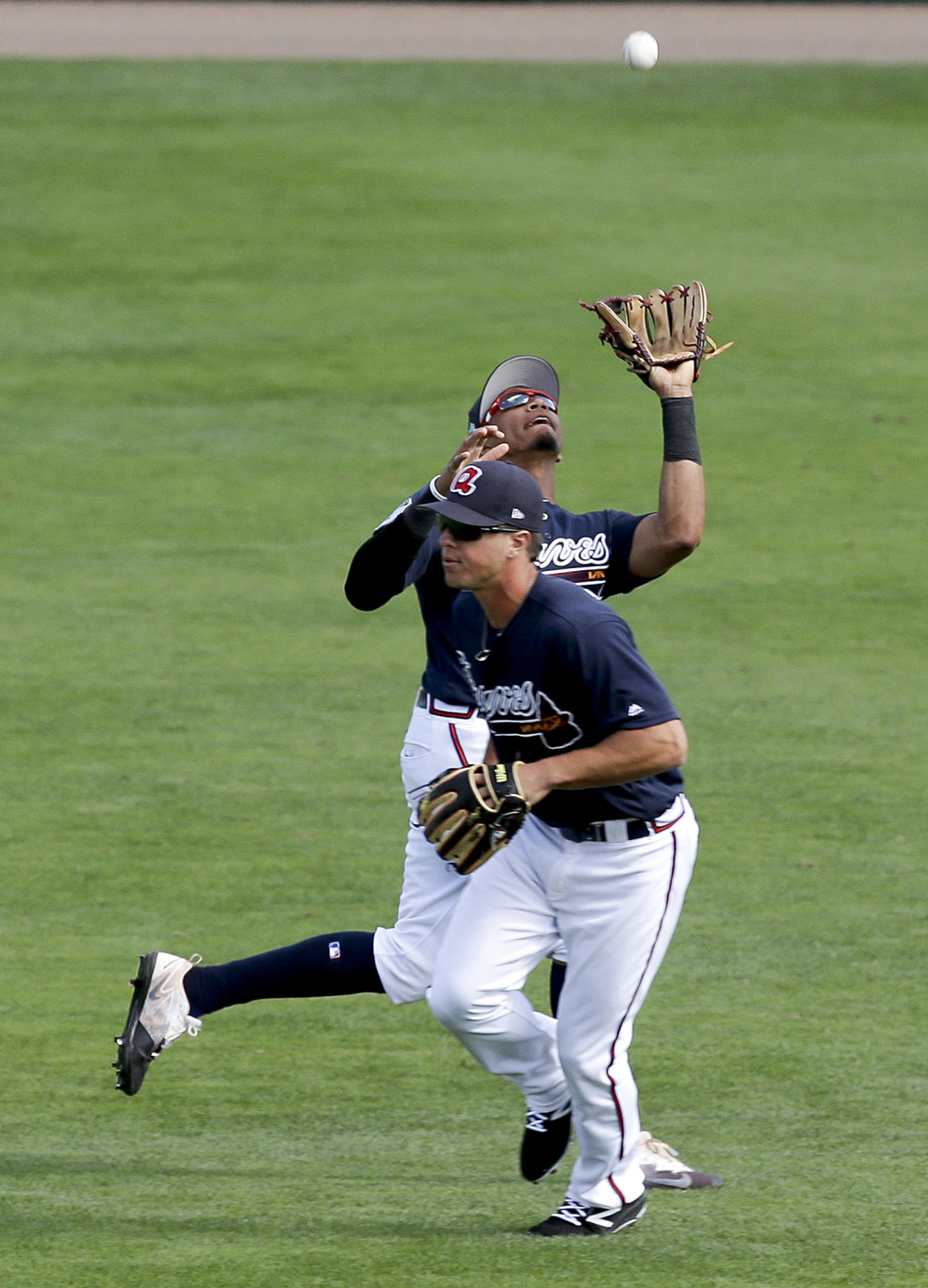 Atlanta Braves shortstop Johan Camargo, rear, catches a pop up as he avoids colliding with second baseman Dylan Moore in the sixth inni...