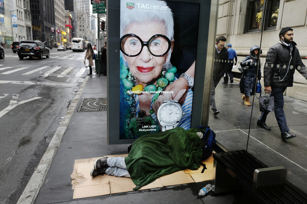 FILE -In this Dec. 5, 2016 file photo, a homeless man sleeps under a blanket in a Fifth Avenue bus shelter in New York. New York City's...