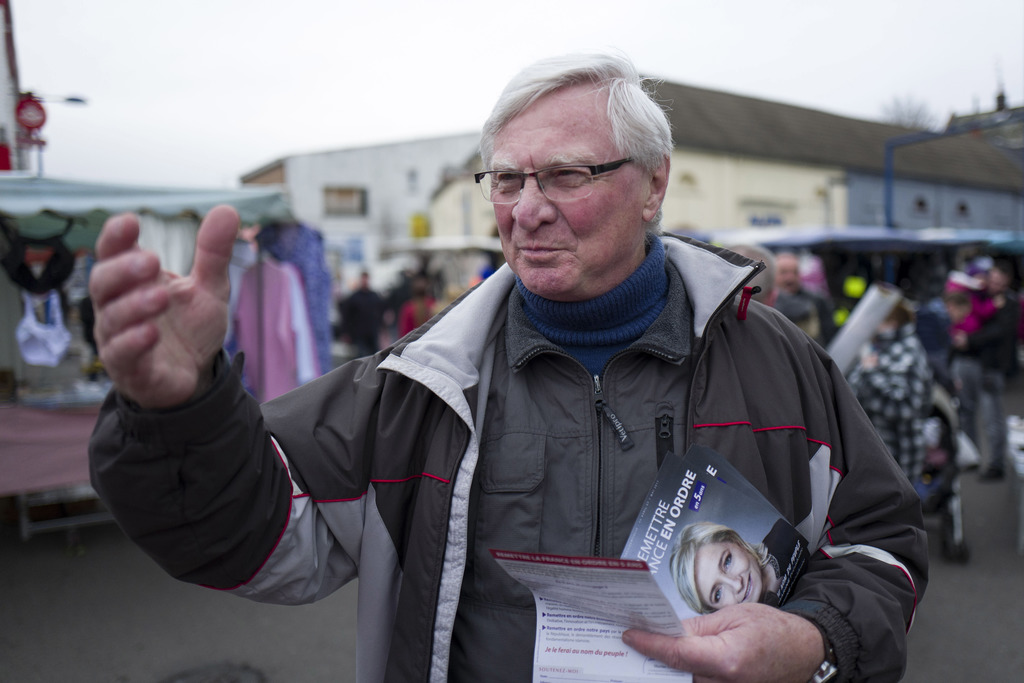 In this Sunday, Feb. 26, 2017 photo, former communist, Jose Evrard,  who is now a member of the Far Right, distributes campaign flyers ...