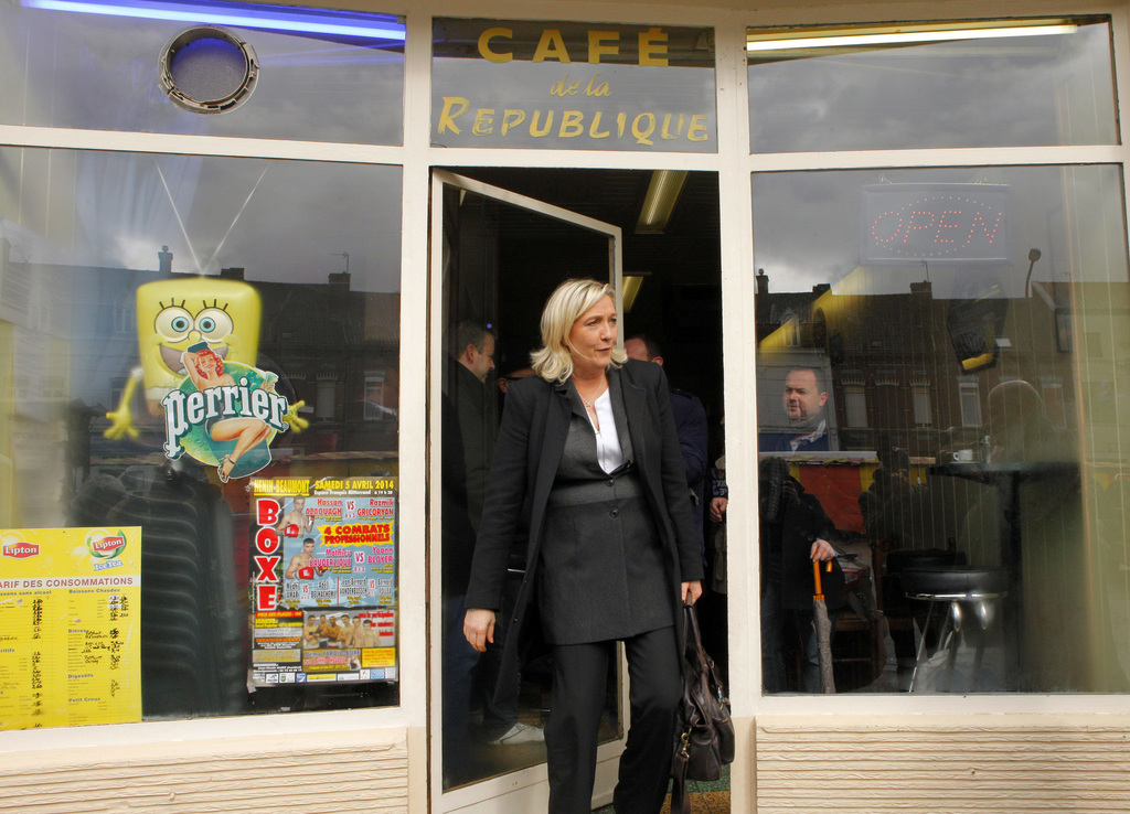 FILE - In this March 21 , 2014 file photo, French far-right party leader Marine Le Pen exits a cafe in Henin-Beaumont, northern France....