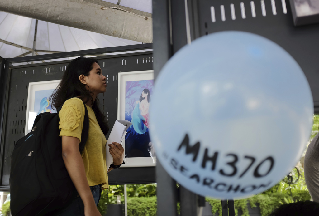 A woman looking at a painting exhibition during the Day of Remembrance for MH370 event in Kuala Lumpur, Malaysia on Saturday, March 4, ...