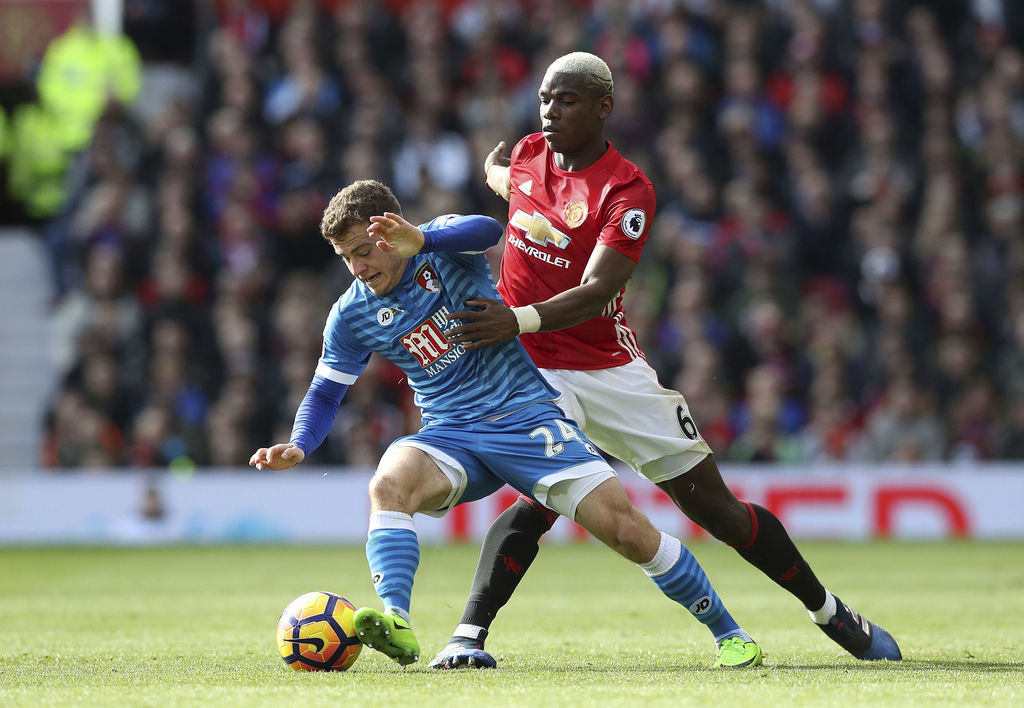 AFC Bournemouth's Ryan Fraser, left, and Manchester United's Paul Pogba battle for the ball during their English Premier League soccer ...