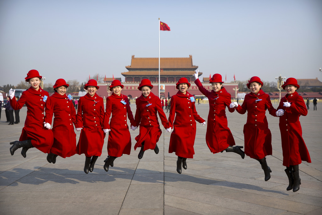 In this Saturday, March 4, 2017, photo, bus ushers leap as they pose for a group photo at Tiananmen Square during a plenary session of ...
