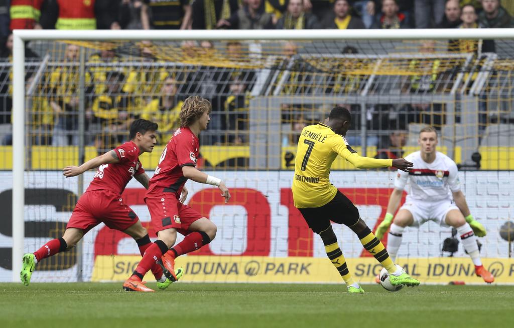 Dortmund's Ousmane Dembele, second right, scores against Leverkusen goalie  Bernd Leno, right, during the German Bundesliga soccer matc...