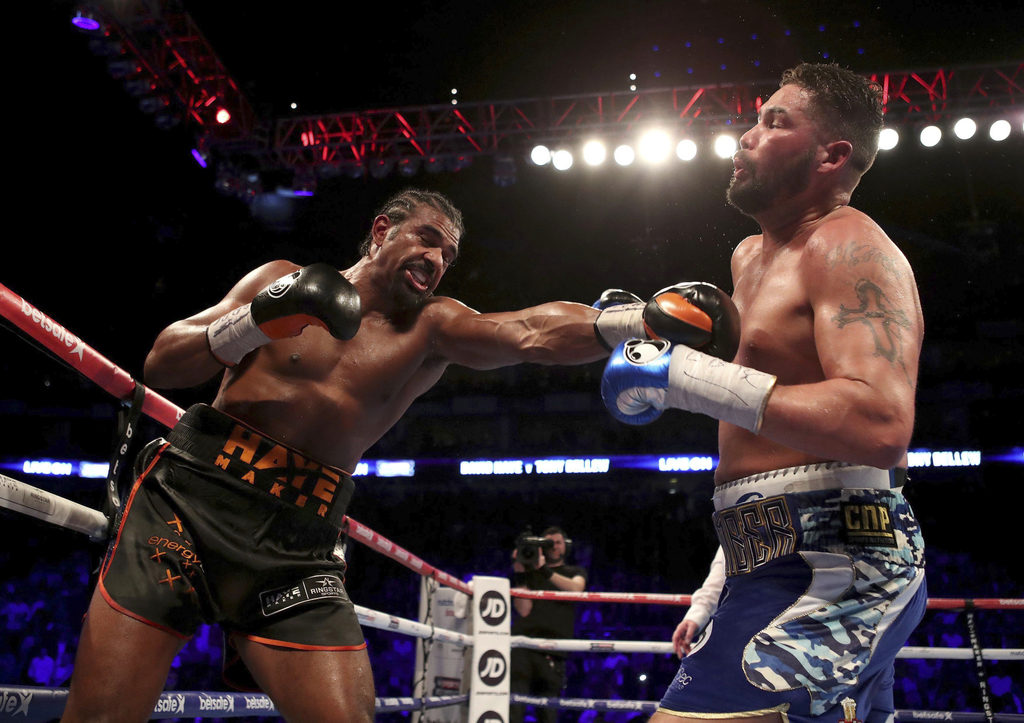 Britain's Tony Bellew, right, gets a punch from his countryman David Haye during their heavyweight contest at the O2 Arena in London Sa...