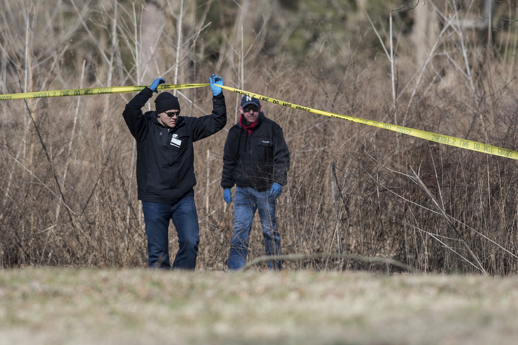 Bartholomew County coroner Clayton Nolting, left, walks under police tape after the body of Jacqueline Watts was discovered in Columbus...