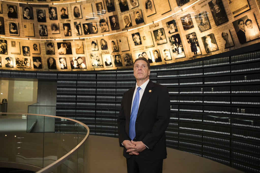 The Governor of New York Andrew M. Cuomo looks at pictures of Jews killed during the Holocaust, in the Hall of Names at Yad Vashem Holo...