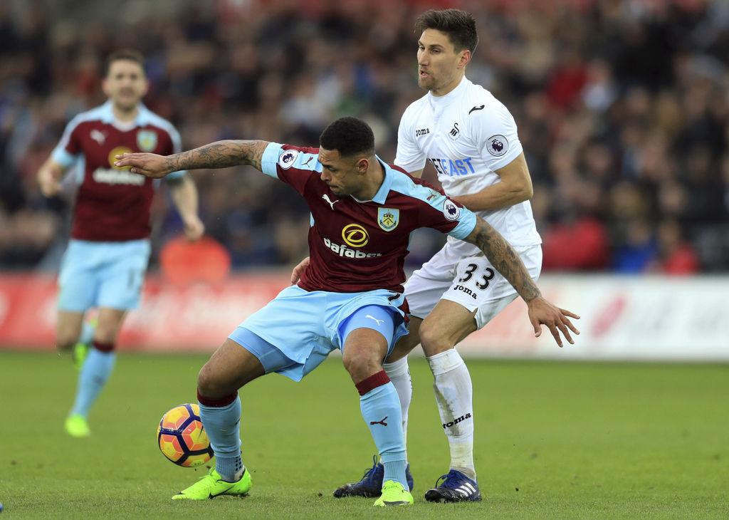 Burnley's Andre Gray, left, and Swansea City's Federico Fernandez battle for the ball during their English Premier League soccer match ...