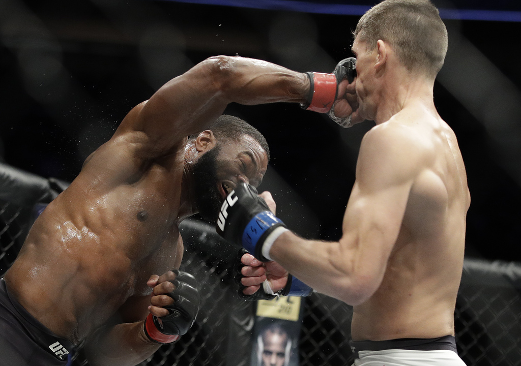 Tyron Woodley, left, hits Stephen Thompson in a welterweight championship mixed martial arts bout at UFC 209, Saturday, March 4, 2017, ...