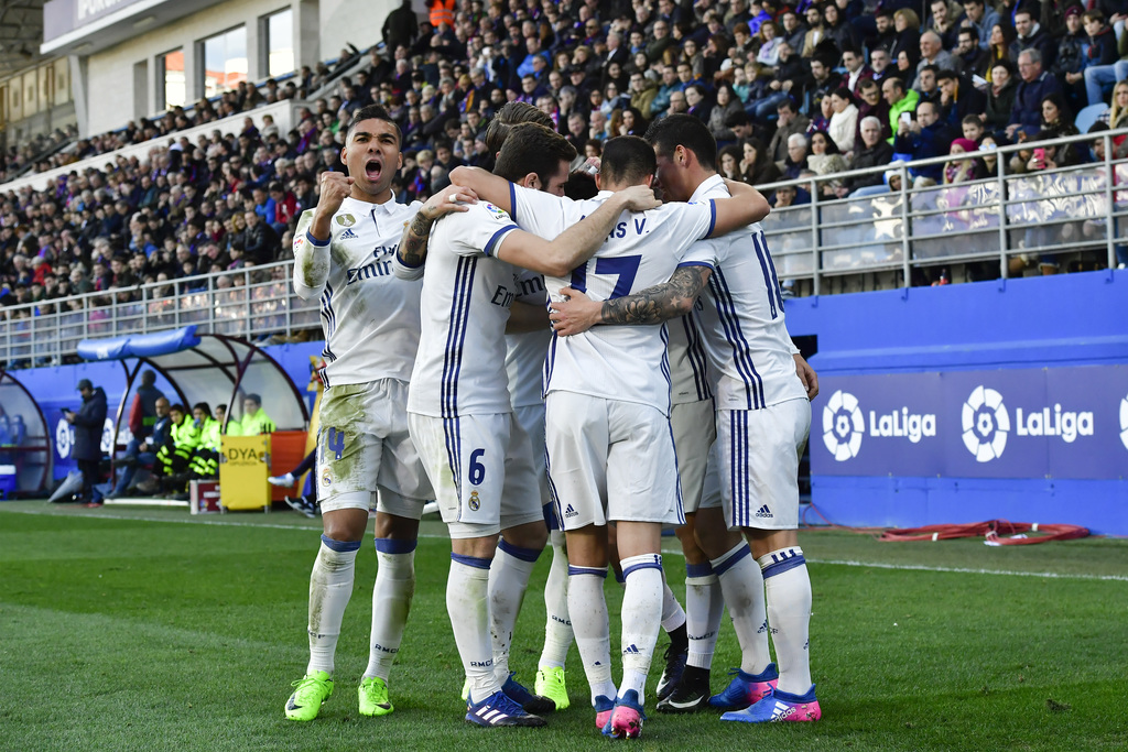 Real Madrid's Henrico Casemiro, left, celebrates after teammate Marco Asensio, obscured from view, scored their forth goal during the S...