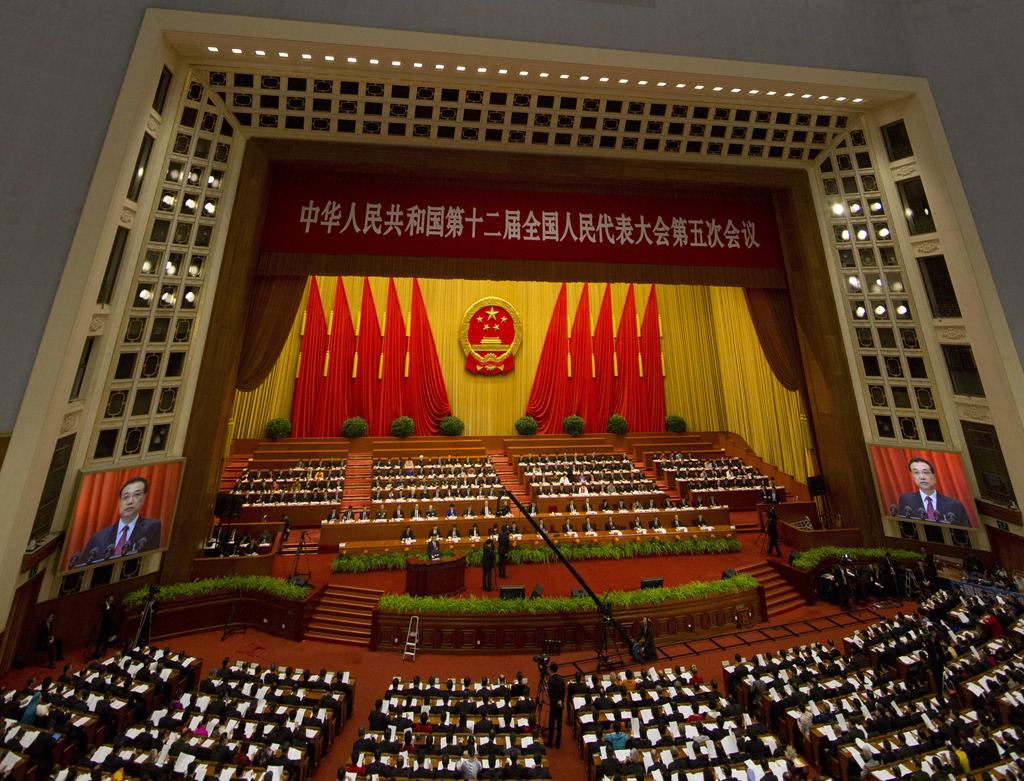 Chinese Premier Li Keqiang is displayed on screens as he delivers a work report at the opening session of the annual National People's ...