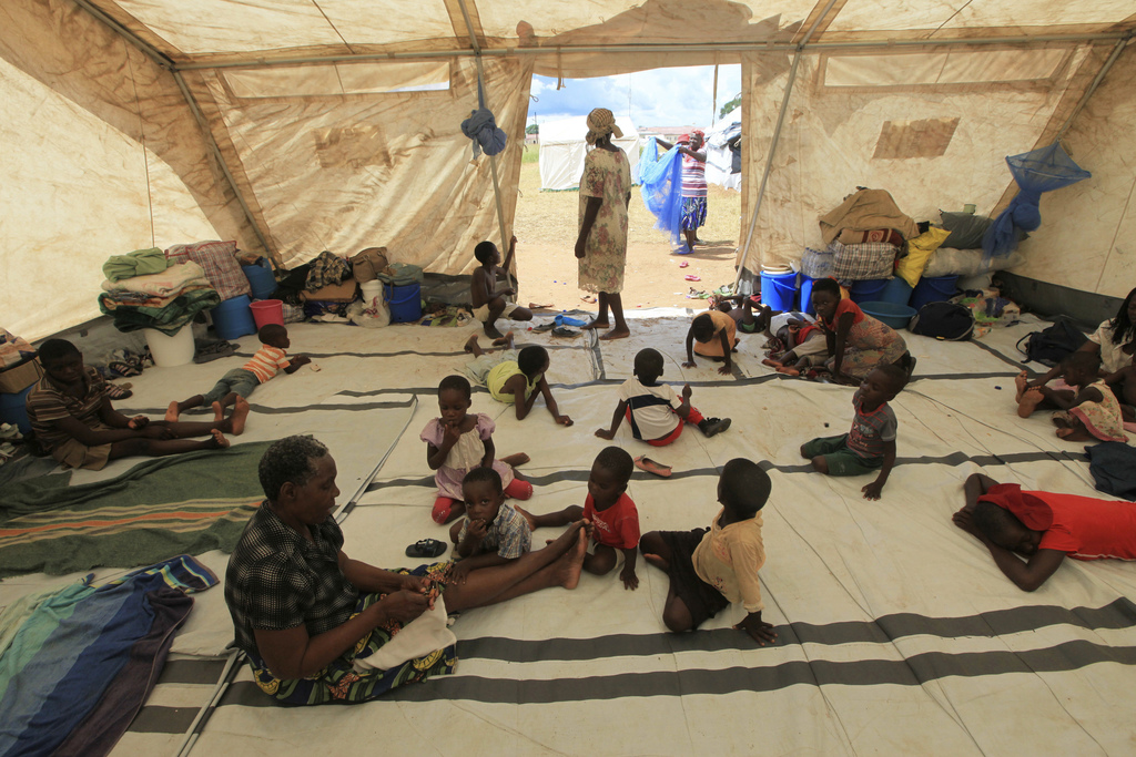 Children sit  inside a tent at a camp set up for flood victims in Tsholostho about 200 kilometres north of Bulawayo, Saturday, March 4,...
