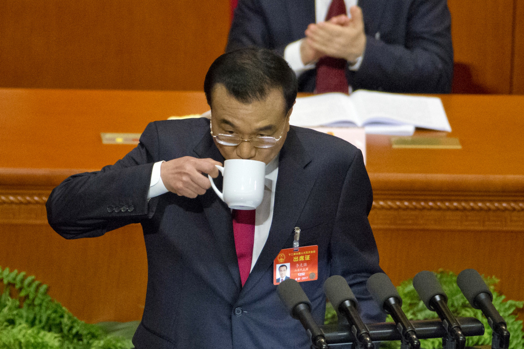 Chinese Premier Li Keqiang sips from cup as he delivers the work report at the opening session of the annual National People's Congress...