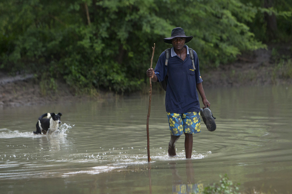 A man crosses a flooded river with his dog in Tsholostho about 200 kilometres north of Bulawayo, Saturday, March 4, 2017. Zimbabwe says...