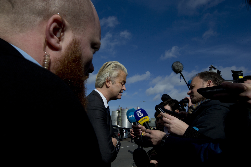 A body guard watches over firebrand anti Islam lawmaker Geert Wilders, center, as he answers questions during an election campaign stop...