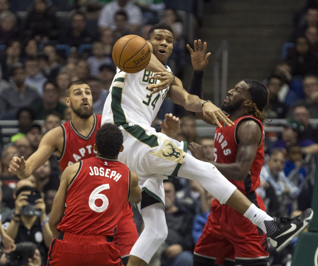 Milwaukee Bucks' Giannis Antetokounmpo passes the ball out after being stopped by Toronto Raptors' Jonas Valanciunas, left, DeMarre Car...