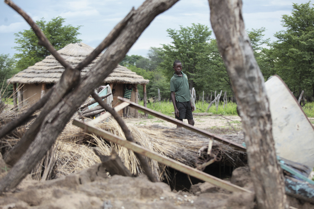 A young boy stands next to a family hut that was destroyed by floods in Tsholostho, about 200 kilometers north of Bulawayo, Saturday, M...