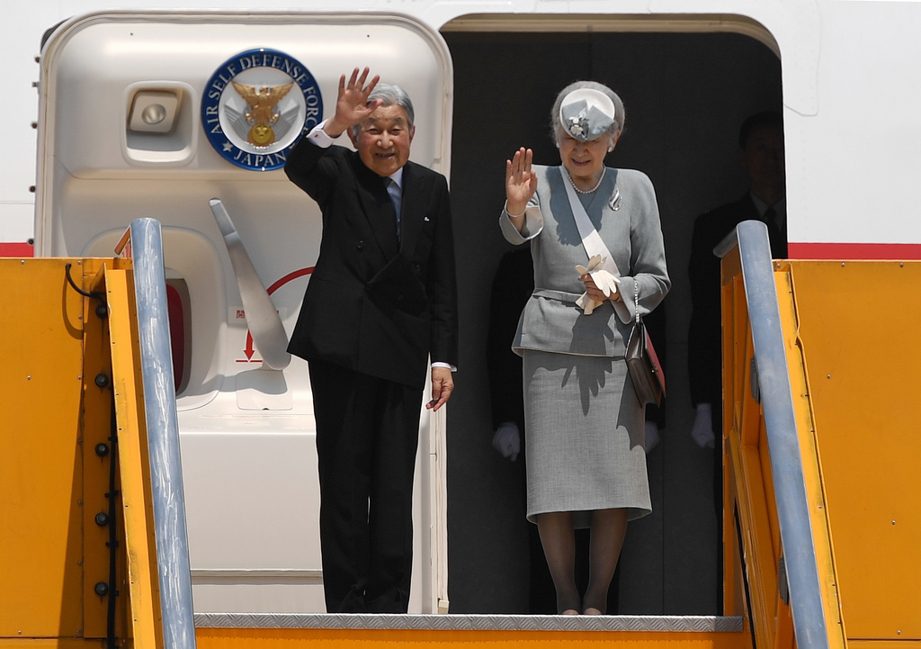 Japan's Emperor Akihito and Empress Michiko wave to bid farewell as they departure from the Phu Bai airport in the central city of Hue,...