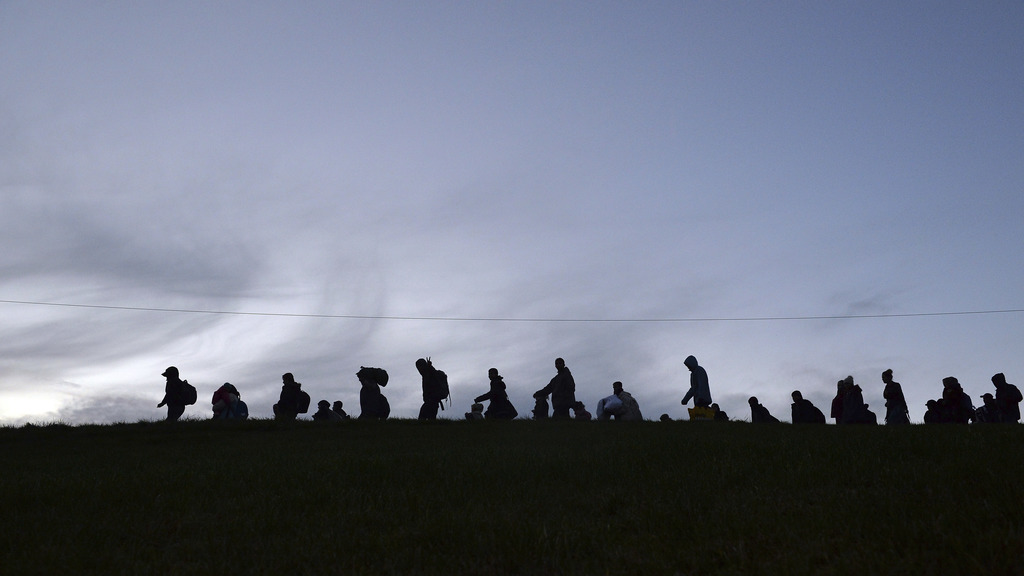 FILE - In this Oct. 28, 2015 file photo German federal police officers guide a group of migrants on their way after crossing the border...