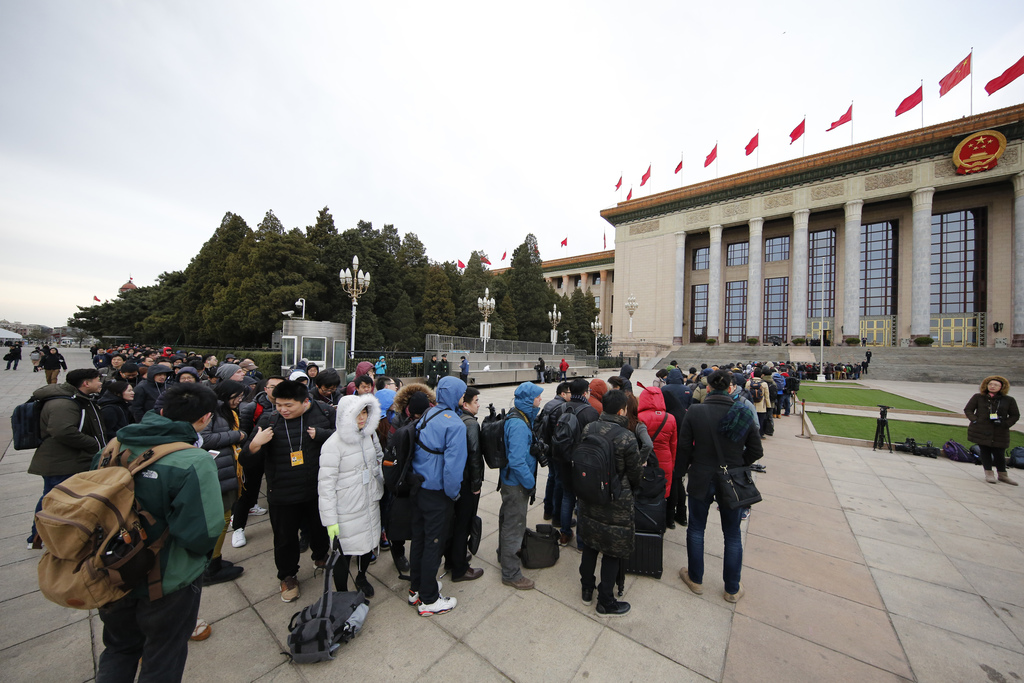 Local and foreign journalists line up to enter the Great Hall of the People to cover the opening session of the annual National People'...